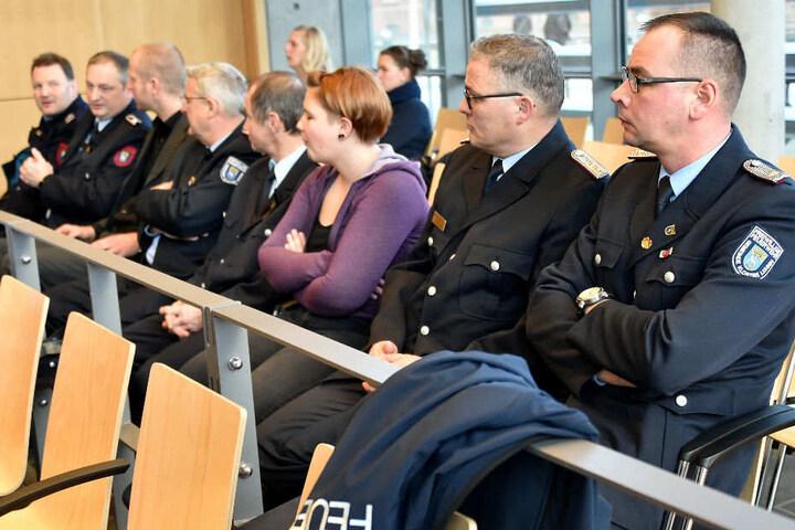 Feuerwehrleute warten im Amtsgericht auf den Prozessbeginn.