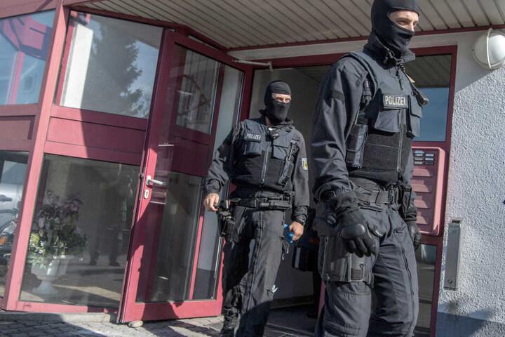 Vermummte Beamte der Bundespolizei kommen aus einem Bordell.