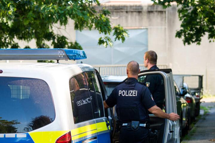 Polizisten stehen neben einem Polizeifahrzeug vor der Justizvollzugsanstalt Lübeck. Hier hat es am Montagnachmittag eine Geiselnahme gegeben.