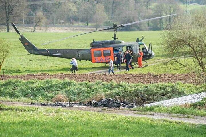 ie Überreste eines abgestürzten und ausgebrannten Ultraleichtflugzeuges sind an einem Feldweg vor einem Rettungshubschrauber zu sehen.