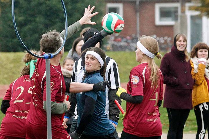 Spielerinnen und Spieler von Ruhr Phoenix (blau) und Münster Marauders (rot) kämpfen um den Ball.