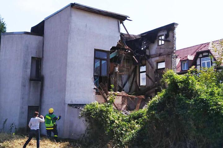 Experten betrachten das eingestürzte Wohnhaus von hinten. Hier läuft auch eine Bahnstrecke entlang.