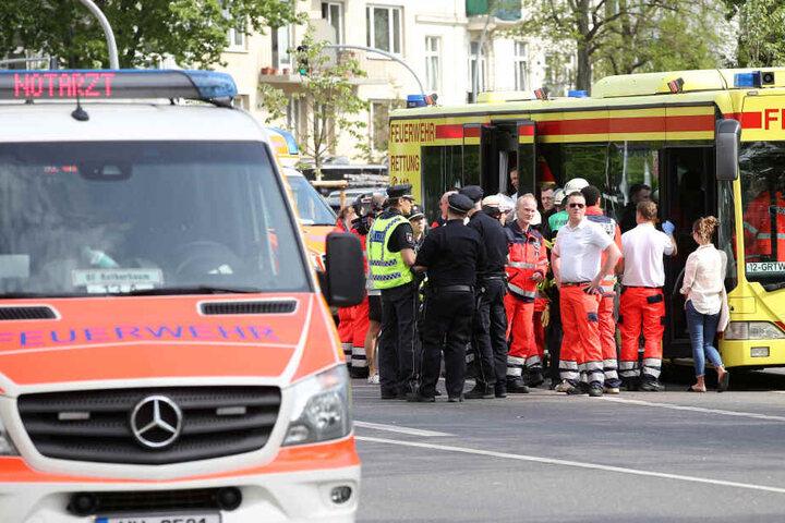 Rettungskräfte und Polizisten stehen vor einem Einsatzfahrzeug zusammen. Im Schanzenviertel war in einem sechsgeschossigem Haus ein Feuer ausgebrochen.