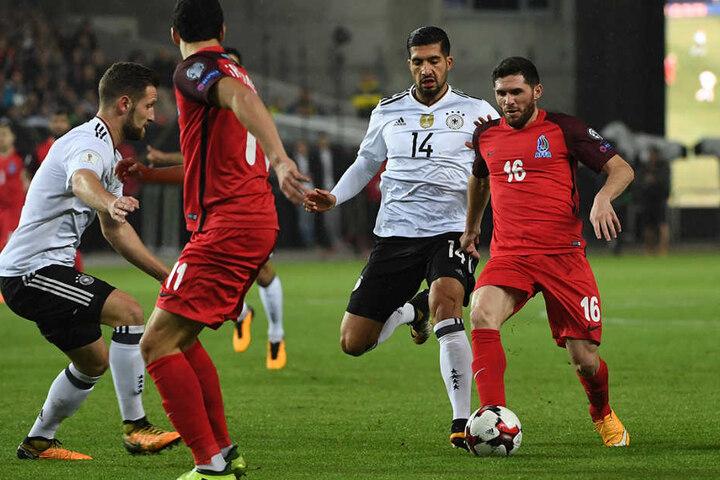 Shkodran Mustafi (l) und Emre Can von Deutschland gegen Javid Hüseynov von Aserbaidschan.