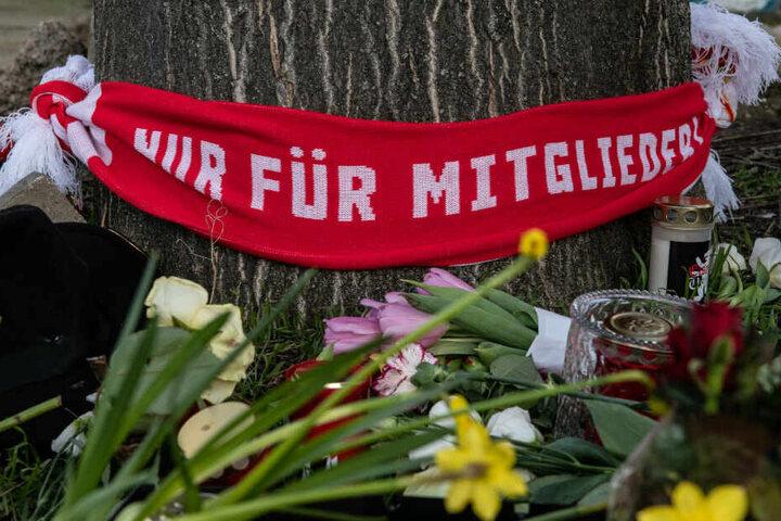 Blumen und Kerzen sowie ein Fan-Schal vom 1. FC Union haben Menschen auf einem Parkplatz an der Stahlheimer Straße abgelegt.
