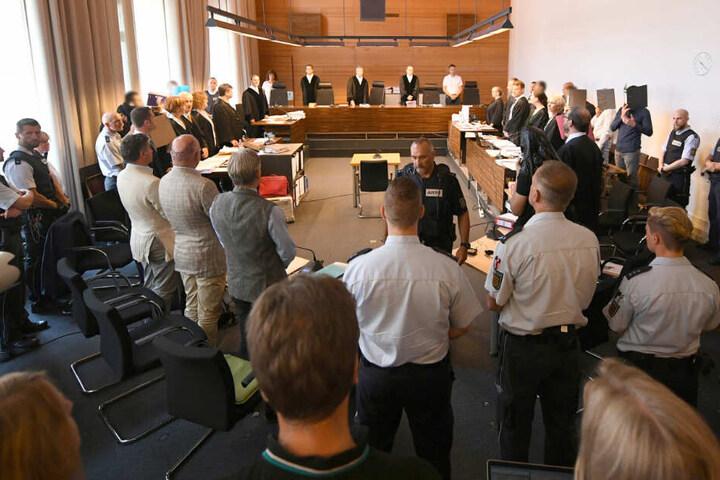 Zu Beginn des Prozesses stehen elf Angeklagte und Justizbeamte im Landgericht seitlich hinter ihren Anwälten. In der Mitte stehen die Richter und Schöffen. (Archivbild)