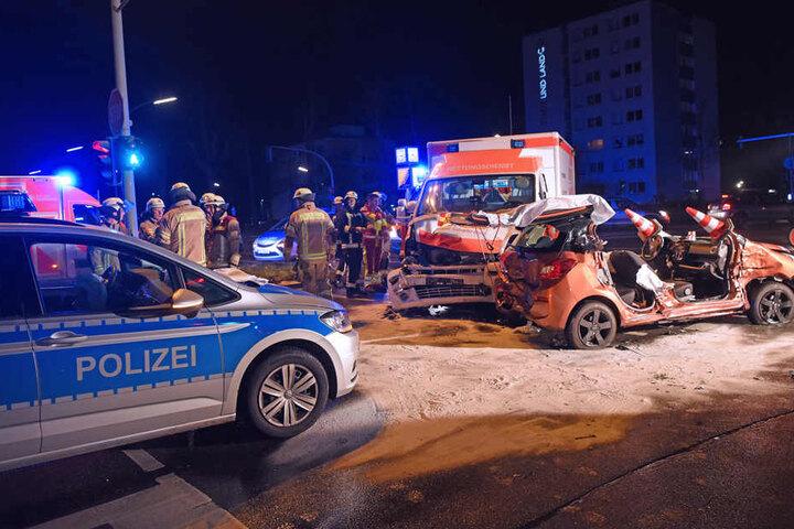 Feuerwehrleute stehen neben einem Pkw, der zuvor mit einem Rettungswagen und Polizeiauto zusammengestoßen war.