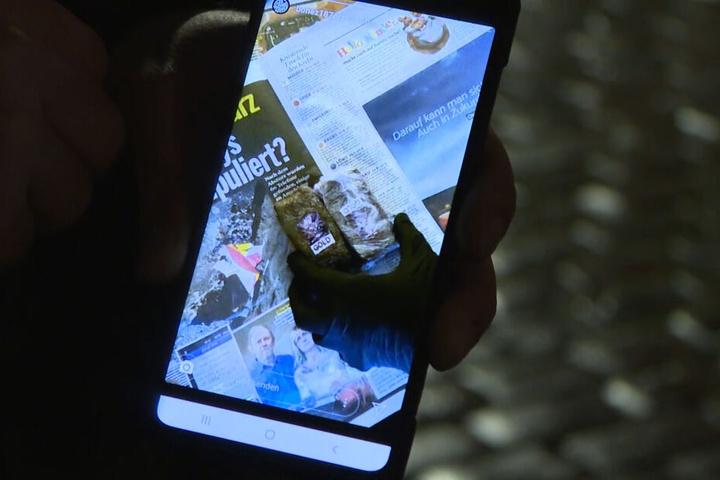Ein Beamter spielt auf einem Handy das Instagram-Video ab.