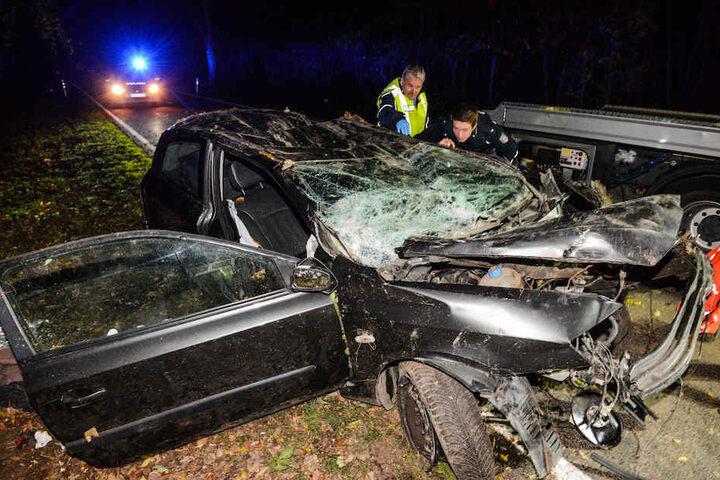 Polizisten begutachten den völlig zerstörten Fiat des Opfers.
