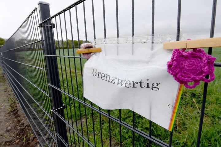 """Ein Zettel mit der Aufschrift """"Grenzwertig"""" hängt am Wildschweinzaun an der deutsch-dänischen Grenze."""