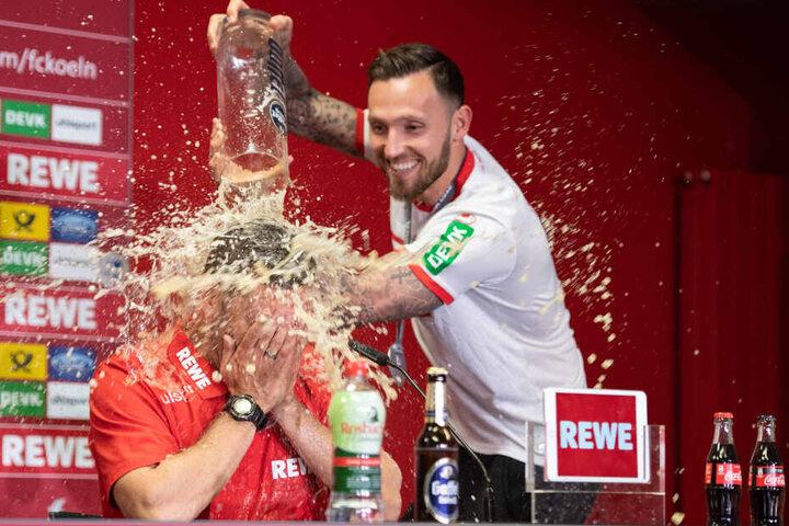 Kölns Marco Höger verpasst Interimstrainer Andre Pawlak während der Pressekonferenz eine Bierdusche.