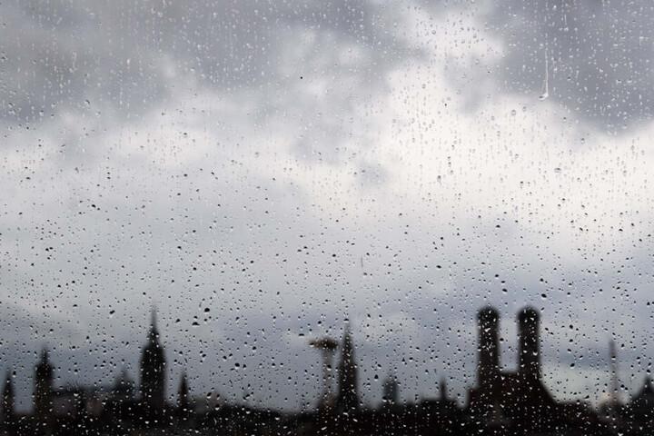 Die Skyline von München ist hinter Tropfen auf einer Fensterscheibe zu sehen.