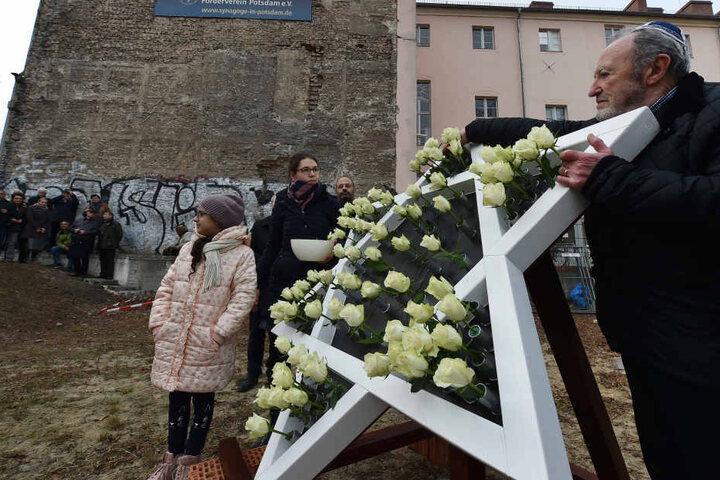 Bei einem Gedenken an die Opfer der Pogromnacht auf der Baustelle der zukünftigen Synagoge schmücken Rosen einen Davidstern.
