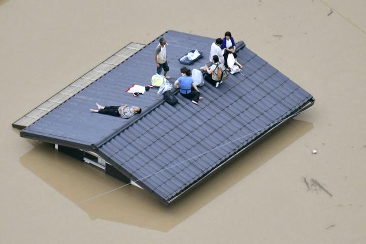 Viele Menschen retten sich auf die Dächer ihrer Häuser und warten auf ihre Evakuierung.