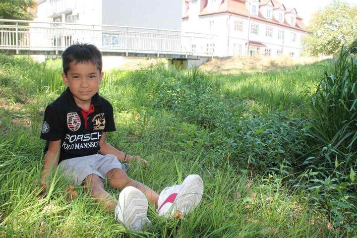 """Hier fließt sonst Wasser: Felipe (6) sitzt im ausgetrockneten """"Elsterfließ"""" in Hoyerswerda."""
