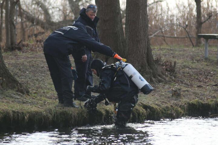 Ein Polizeitaucher kommt aus dem Wasser.