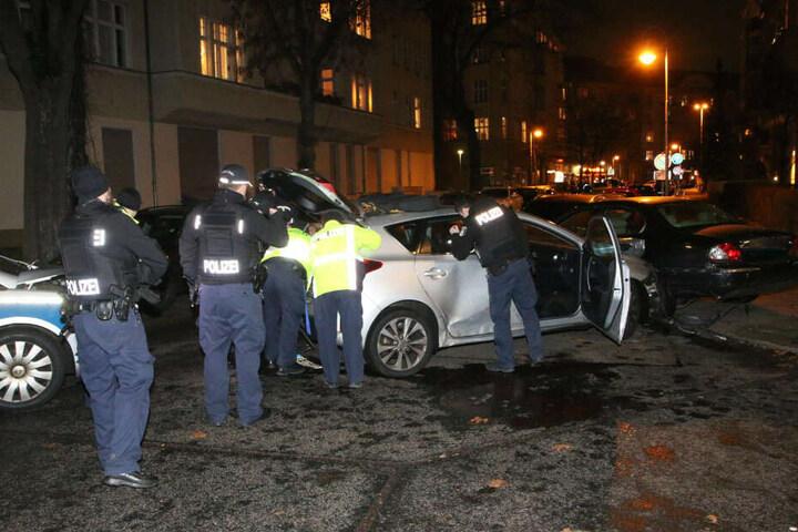 Polizisten untersuchen das Fluchtfahrzeug.