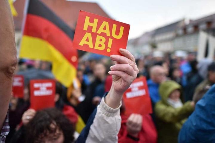 """Eine Demonstrantin zeigt bei Merkels Auftritt in in Finsterwalde eine """"Hau ab""""-Karte."""