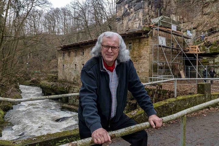 """Herman Häse vor der Lochmühle. Noch ist sie eine Ruine, wurde aber bereits  gesichert. Dahinter auf den Felsen soll das Hotel """"schweben""""."""