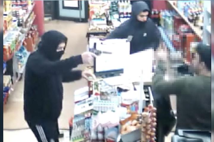 Mit einer Pistole wird der Verkäufer bedroht.
