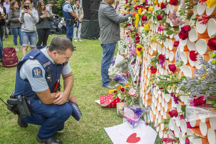 Ein Polizist vor dem behelfsmäßigen Denkmal für die Opfer der Anschläge von Christchurch an der University of Canterbury.