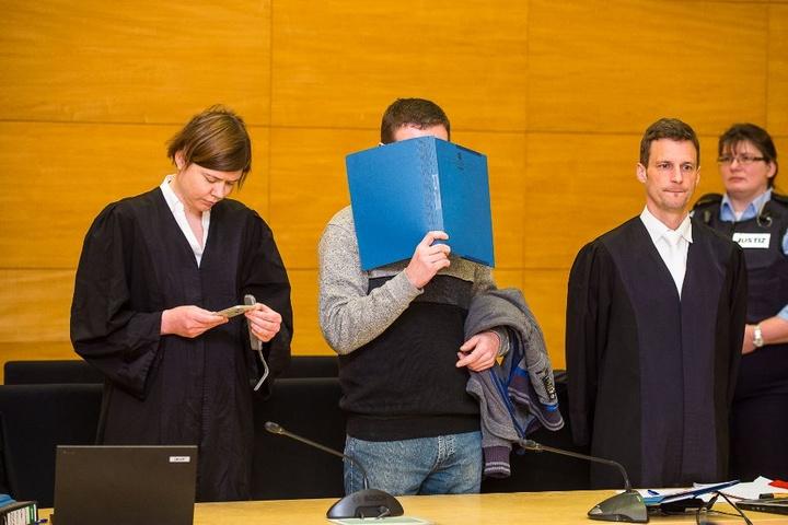 Wie in jeder Verhandlung hält sich der Angeklagte eine Aktenmappe vor das Gesicht. Rechts und links von ihm stehen seine Verteidiger.