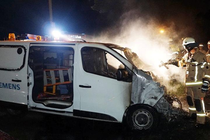 Feuerwehrmänner löschen den brennenden Siemens-Transporter.