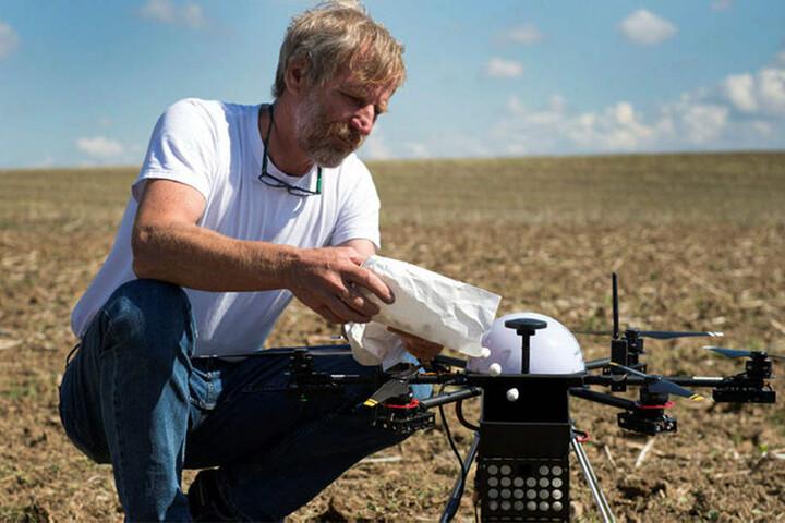 Axel Weckschmied befüllt auf einem Acker in Riemsdorf eine Drohne zur biologischen Bekämpfung des Maiszünslers mit Kugeln, in denen sich Larven der Erzwespe befinden.