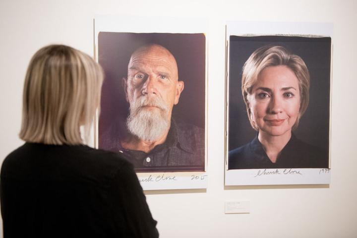 Eine Besucherin vor zwei vergrößerten Polaroids von Hillary Clinton (70) und Chock Close (78).