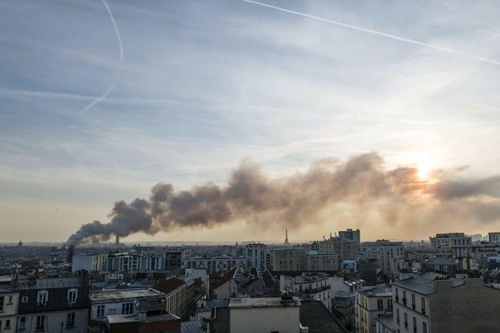 Weit über der Stadt ist die Rauchsäule des Brandes zu sehen.