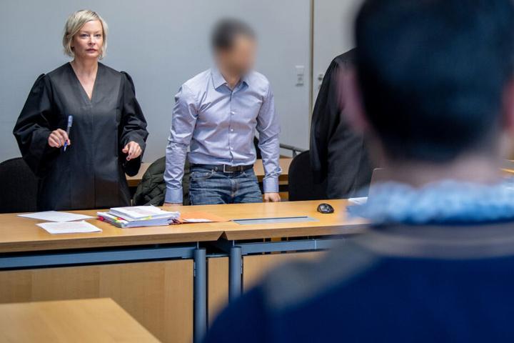 Der Angeklagte (Mitte) steht im Gerichtssaal des Amtsgerichts gegenüber seines Klägers.