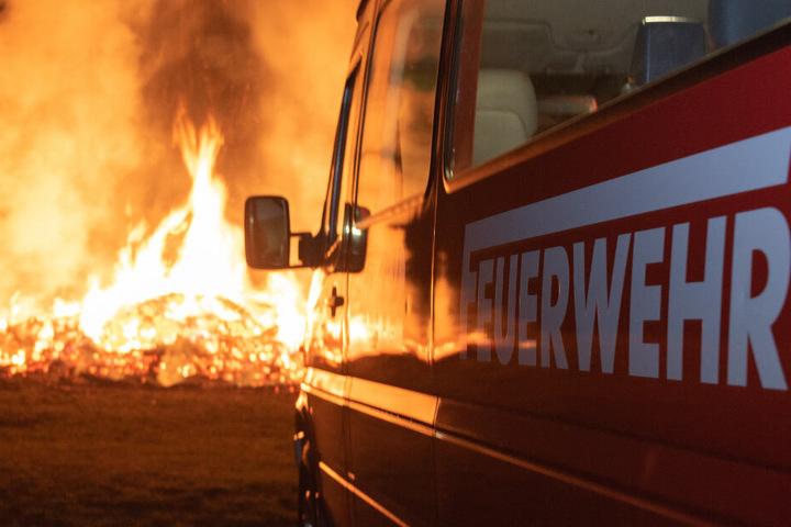 Ein Feuerwehrauto steht vor dem brennenden Osterfeuer.