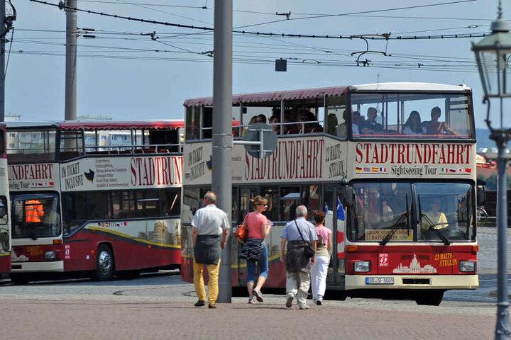Stadtrundfahrt-Busse warten auf dem Dresdner Theaterplatz auf Touristen.