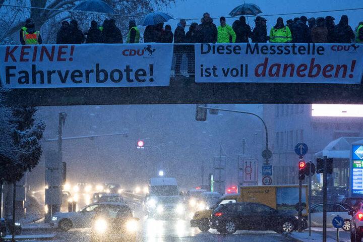 Demonstranten haben während einer Demonstration gegen das Dieselfahrverbot am Neckartor Plakate aufgehängt.