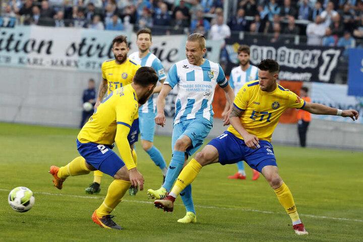 Mittelfeldspieler Dennis Grote von Lok-Spielern umzingelt.