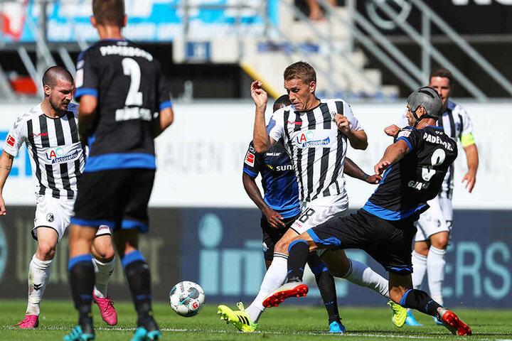 Paderborns Klaus Gjasula (r) im Kampf um den Ball mit Nils Petersen (2.v.r) aus Freiburg.