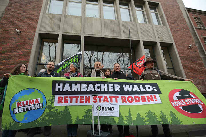Umweltaktivisten und Braunkohlegegener stehen mit einem Transparent vor dem Verwaltungsgericht.