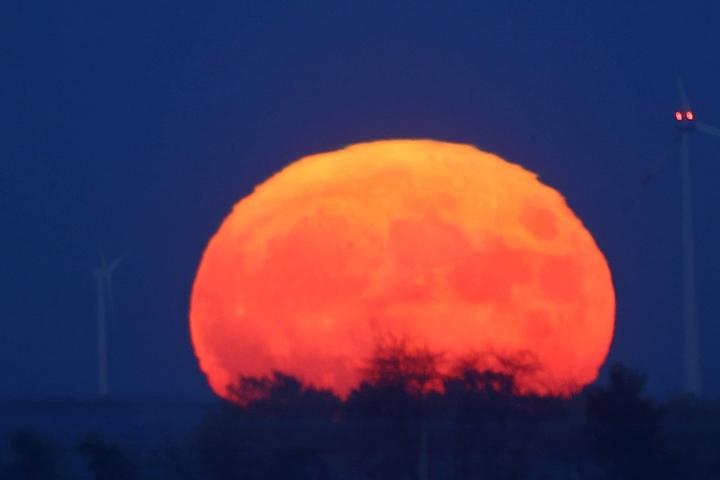 Bei Waldenburg (Landkreis Zwickau) geht der Mond als roter Feuerball auf.
