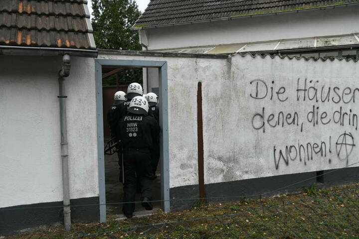 Polizisten gehen in den Hof eines Hauses, das von Braunkohlegegnern besetzt worden war.