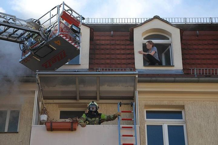 Eine junge Frau klettert aus dem Fenster.