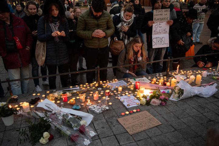 Trauernde stehen nahe dem Straßburger Weihnachtsmarkt hinter zahlreichen brennenden Kerzen.