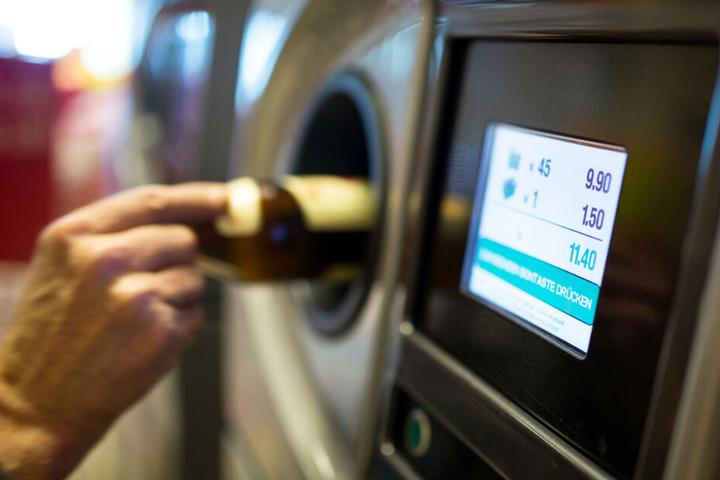 Ein Flaschensammler wirft eine Funde in einen Automaten.