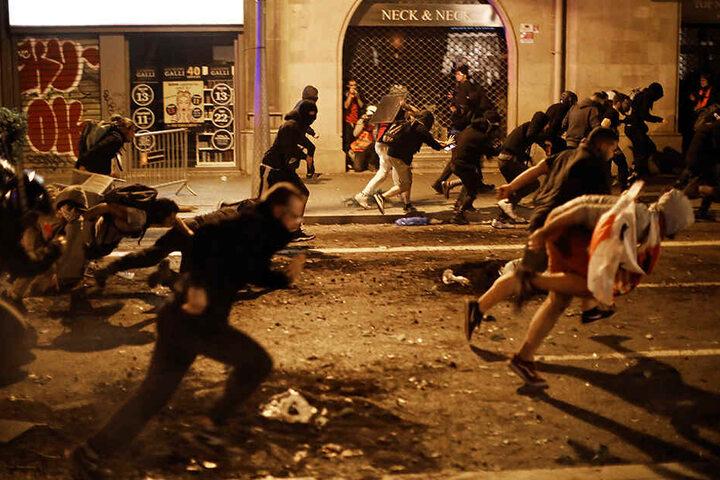 Demonstranten fliehen vor der Polizei. In der Nacht zu Freitag gab es weitere Unruhen im Nordosten Spanien.