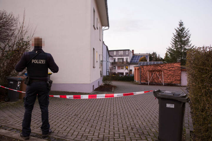 Ein Polizist steht vor einem Absperrband.