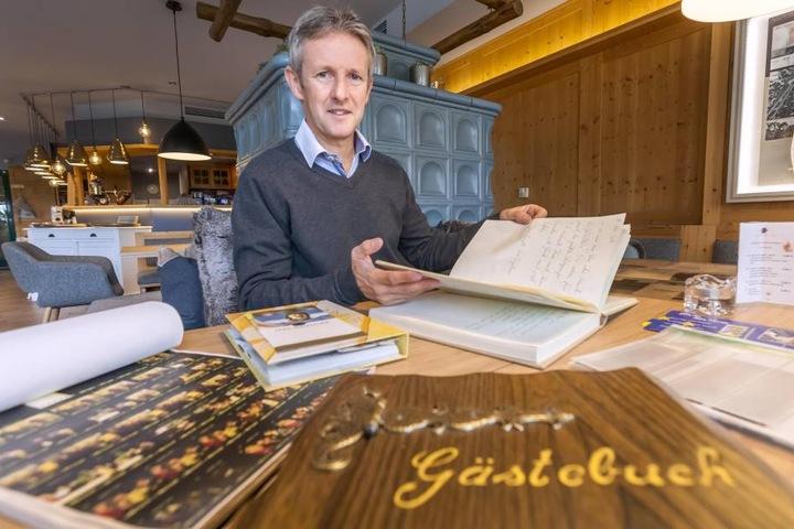 Jens Weissflog blättert in einem Gaestebuch