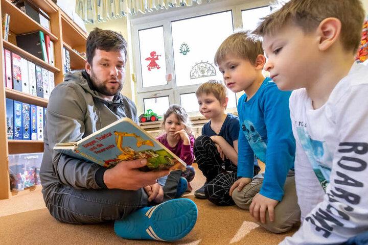 """In der Kita """"Pünktchen"""" arbeitet Tom als Erzieher - liest Hanna (5), Maximilian (6), Milan (6) und Bruno (5, v.l.) eine Geschichte vor."""