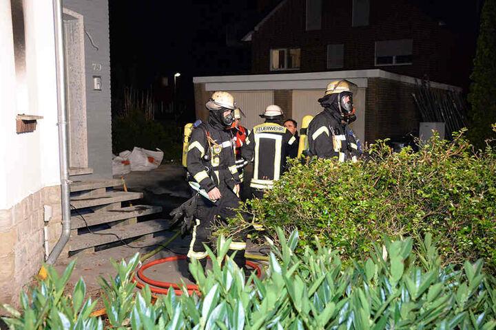 Einige Feuerwehrmänner setzten Atemschutzmasken auf.