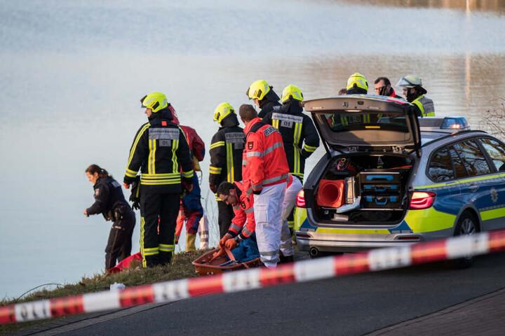 Einsatzkräfte der Polizei und Feuerwehr stehen an einem Gewässer. (Symbolfoto)