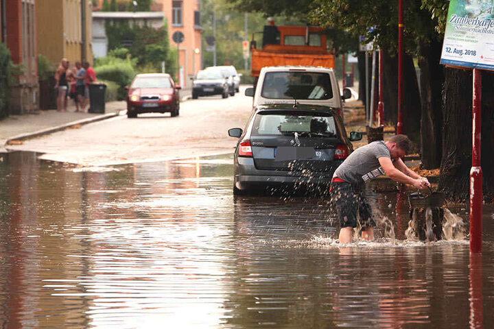 Nach dem Sturzregen watet ein Freitaler durch das tiefe Wasser.