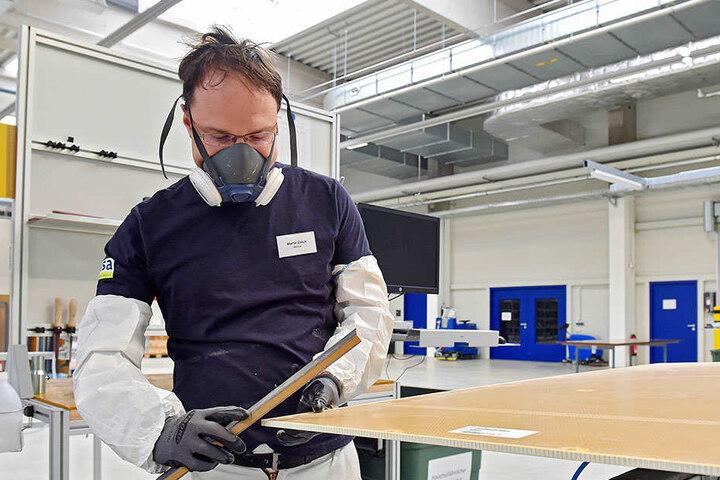 Mitarbeiter Martin Ullrich (31) säubert die Kanten der Frachtraumverkleidung. Im Fachjargon heißt das entgraten.